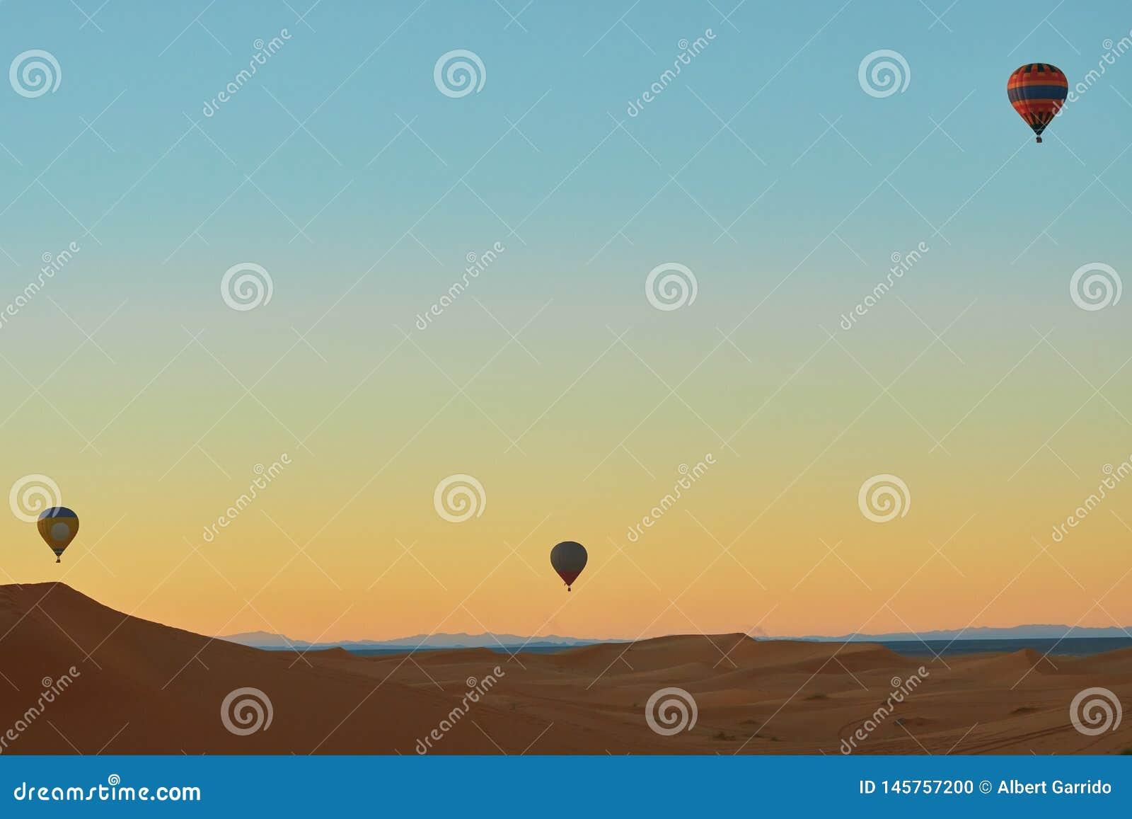 Voo do balão de ar três quente sobre o deserto