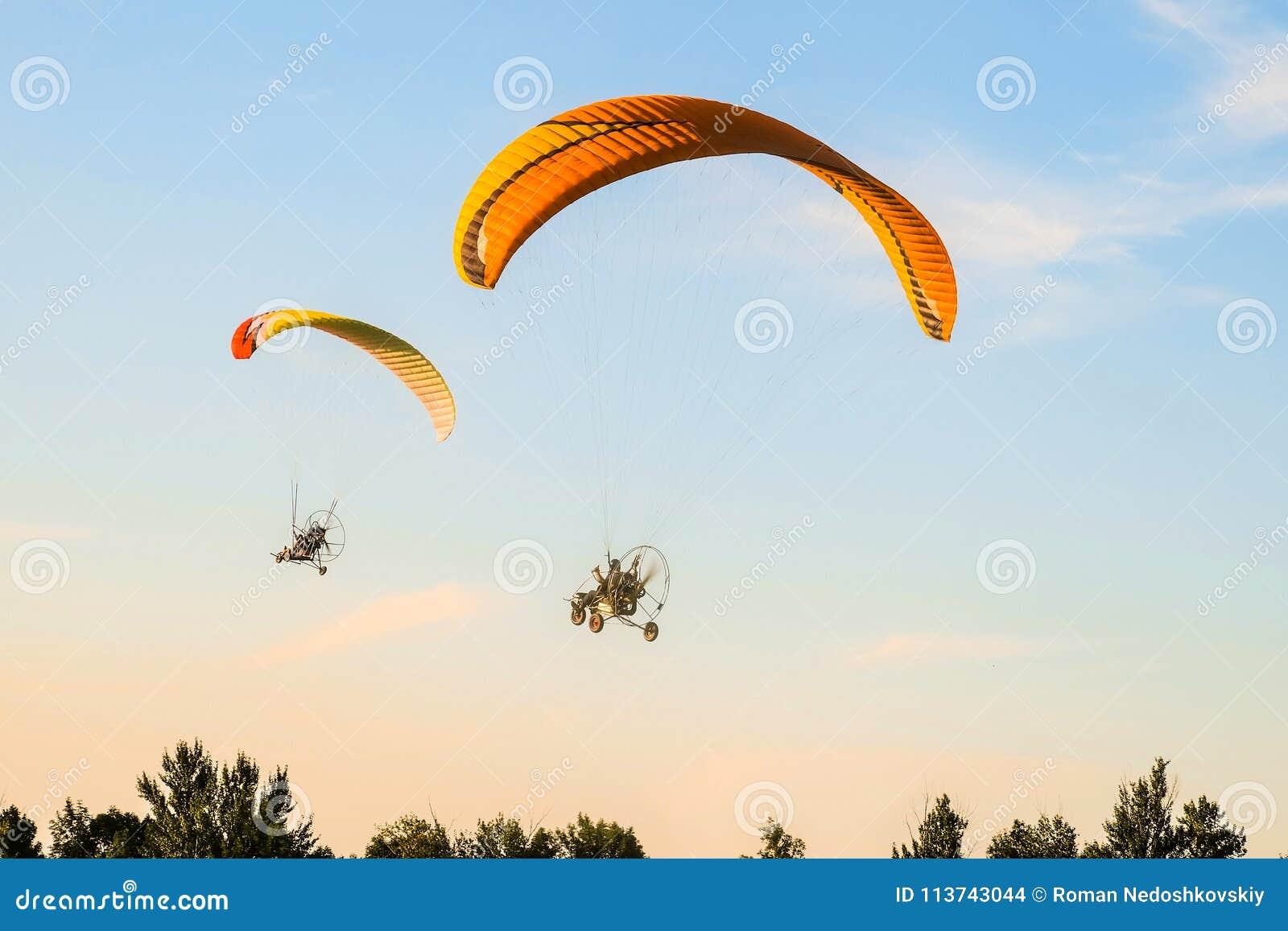 Voo do trike de dois paragliders do motor em direção ao céu