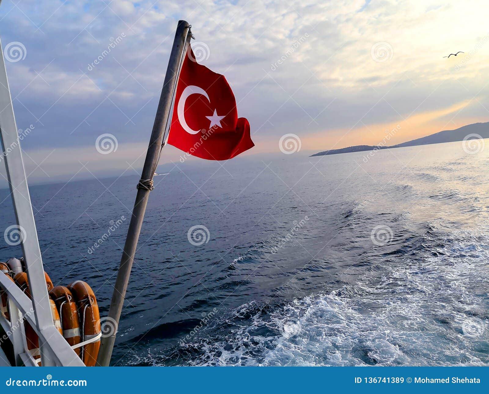 Voo turco da bandeira durante a partida da ilha das princesas em Istambul no por do sol