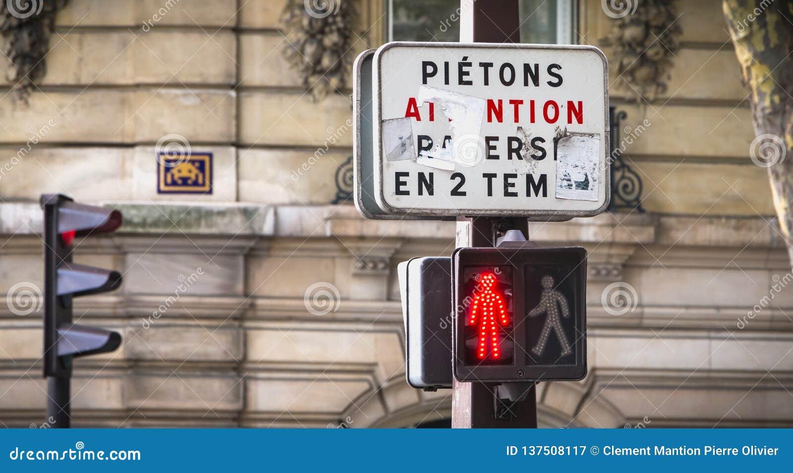 Voor een tricolorverkeerslicht, wijst op een teken in het Frans aan voetgangers om in twee stadia te kruisen