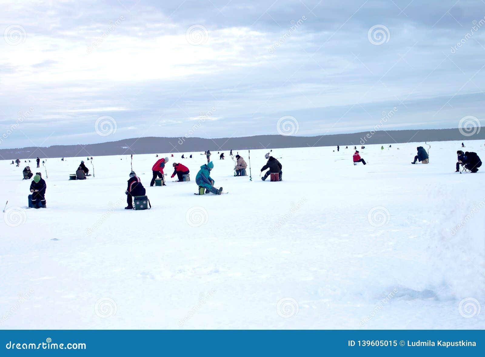 Voor een zonnige de winterdag, zijn er vissers die op een groot meer zitten