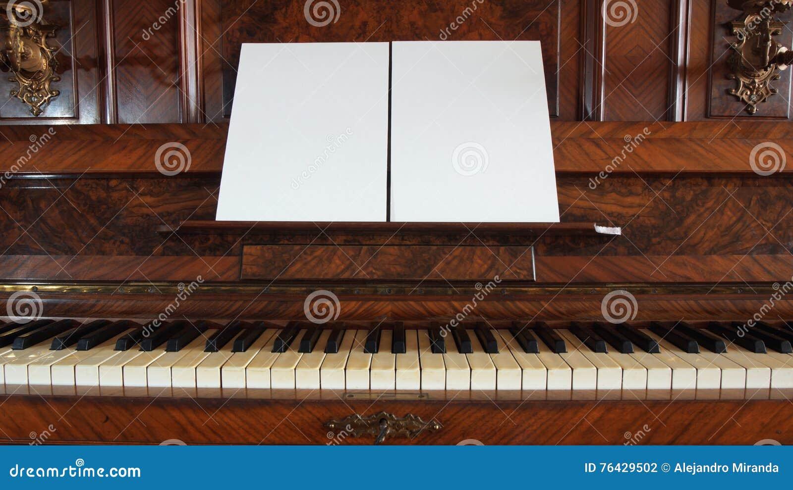 Vooraanzicht van een antieke piano met het open toetsenbord en twee bladen van leeg document op steun voor muzieknoten