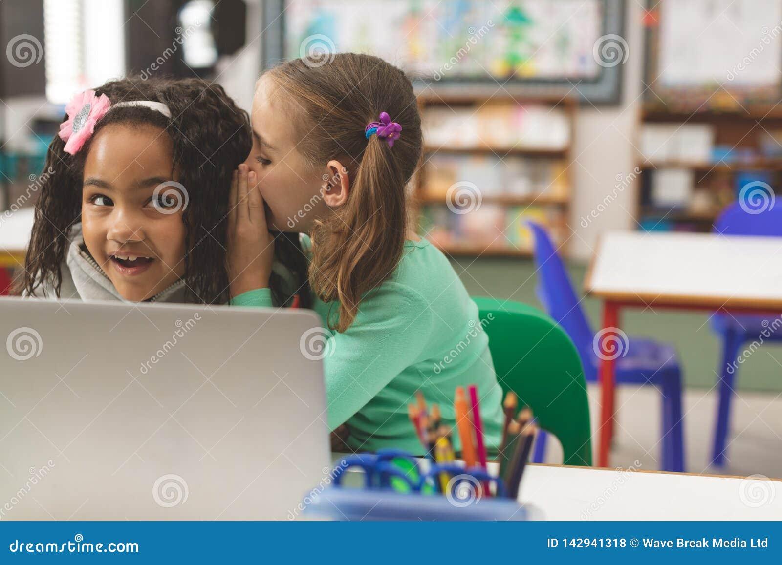 Vooraanzicht van Kaukasisch schoolmeisje die een geheim fluisteren in vriendenoor terwijl haar vriend astonis schijnt