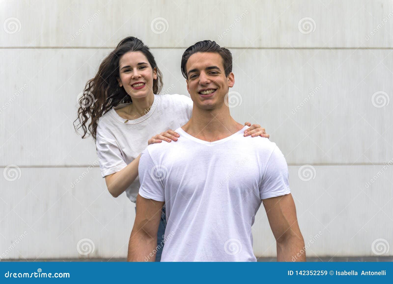 Vooraanzicht van mooi jong, camera bekijken en paar die terwijl in openlucht status glimlachen koesteren