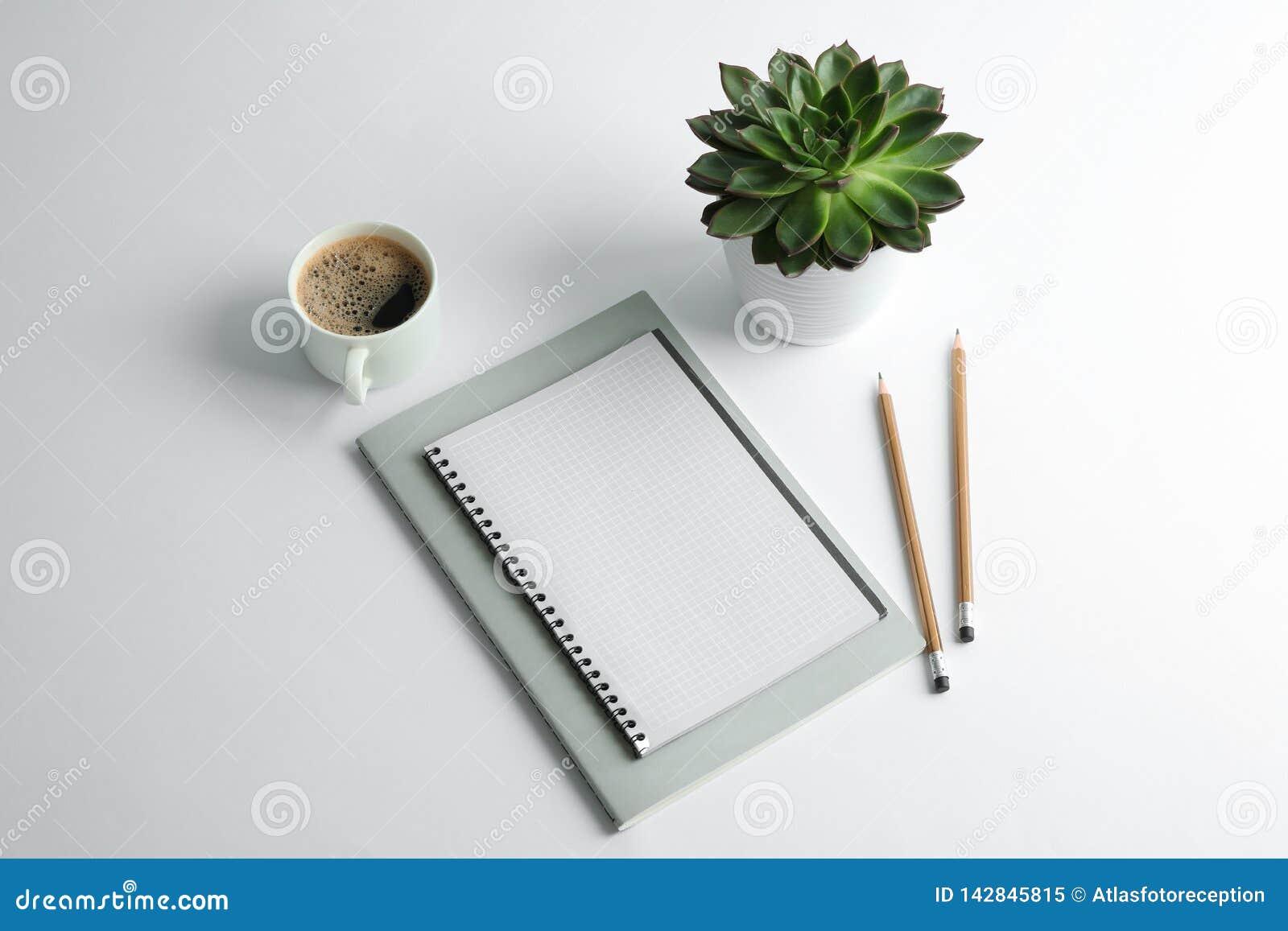 Voorbeeldenboeken, kop van koffie, potloden en succulente installatie op witte achtergrond