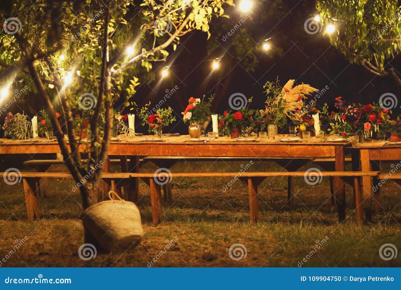 Voorbereide lijst voor een rustiek openluchtdiner bij nacht met winegla