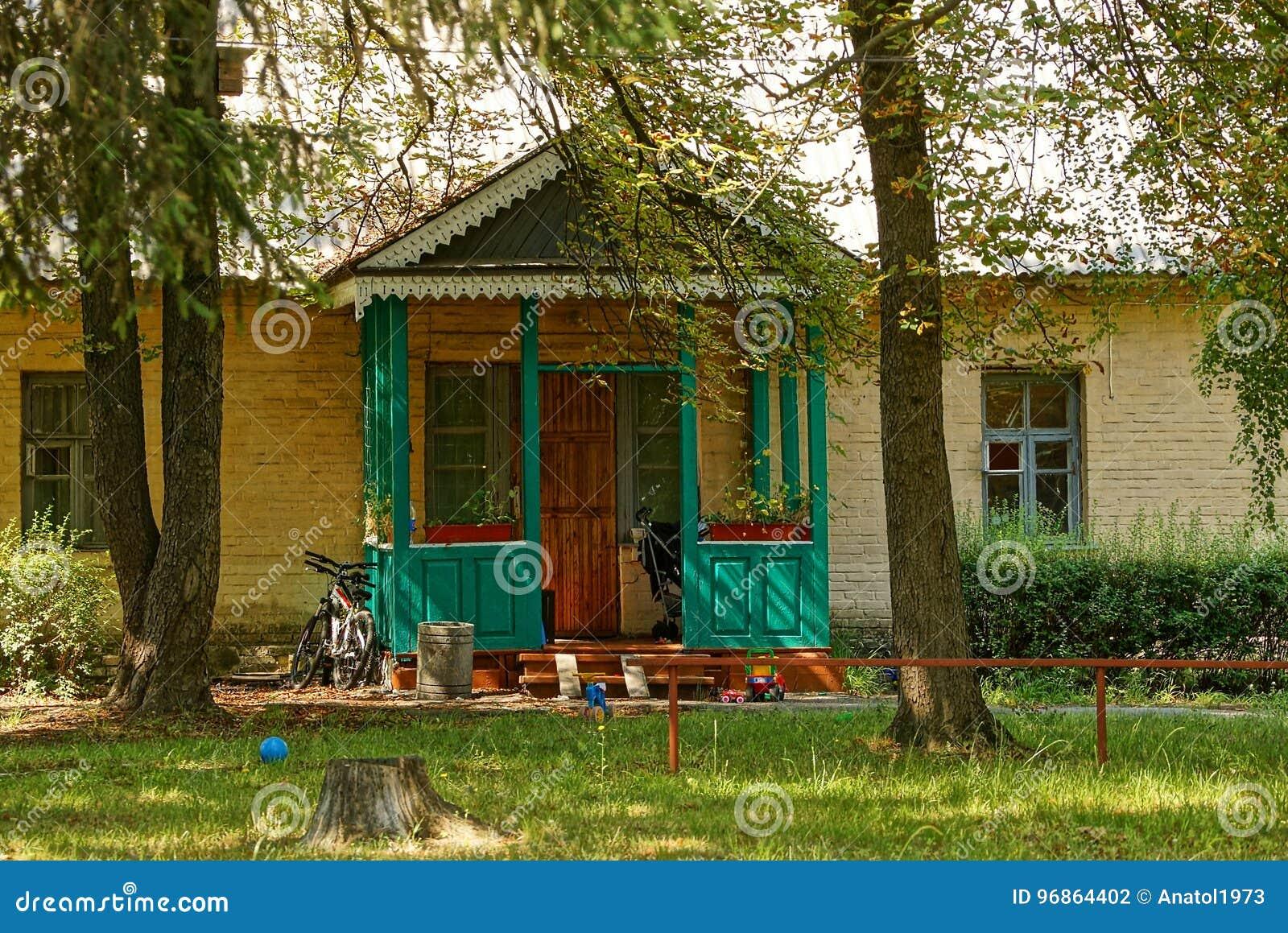 Voorgevel van een landelijk huis met een veranda voor een gazon en