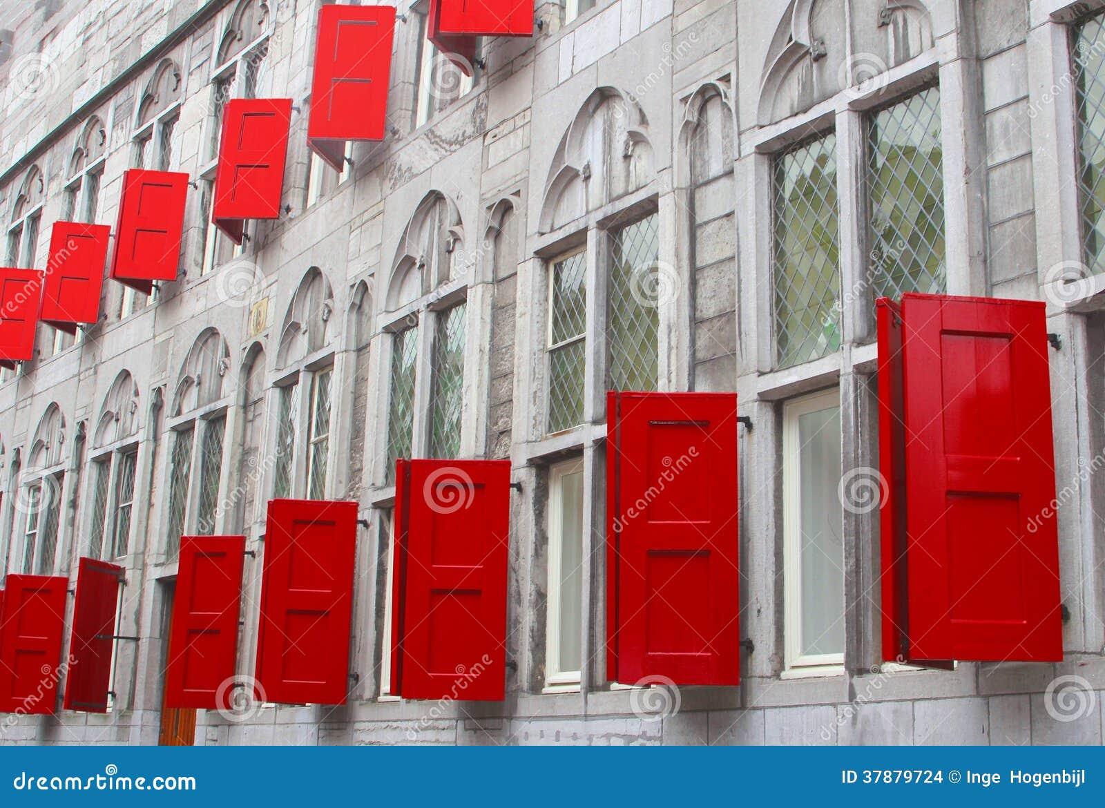 Voorgevel van een oud gebouw met rode schuilplaatsen en gebrandschilderd glasvensters, Utrecht, Nederland