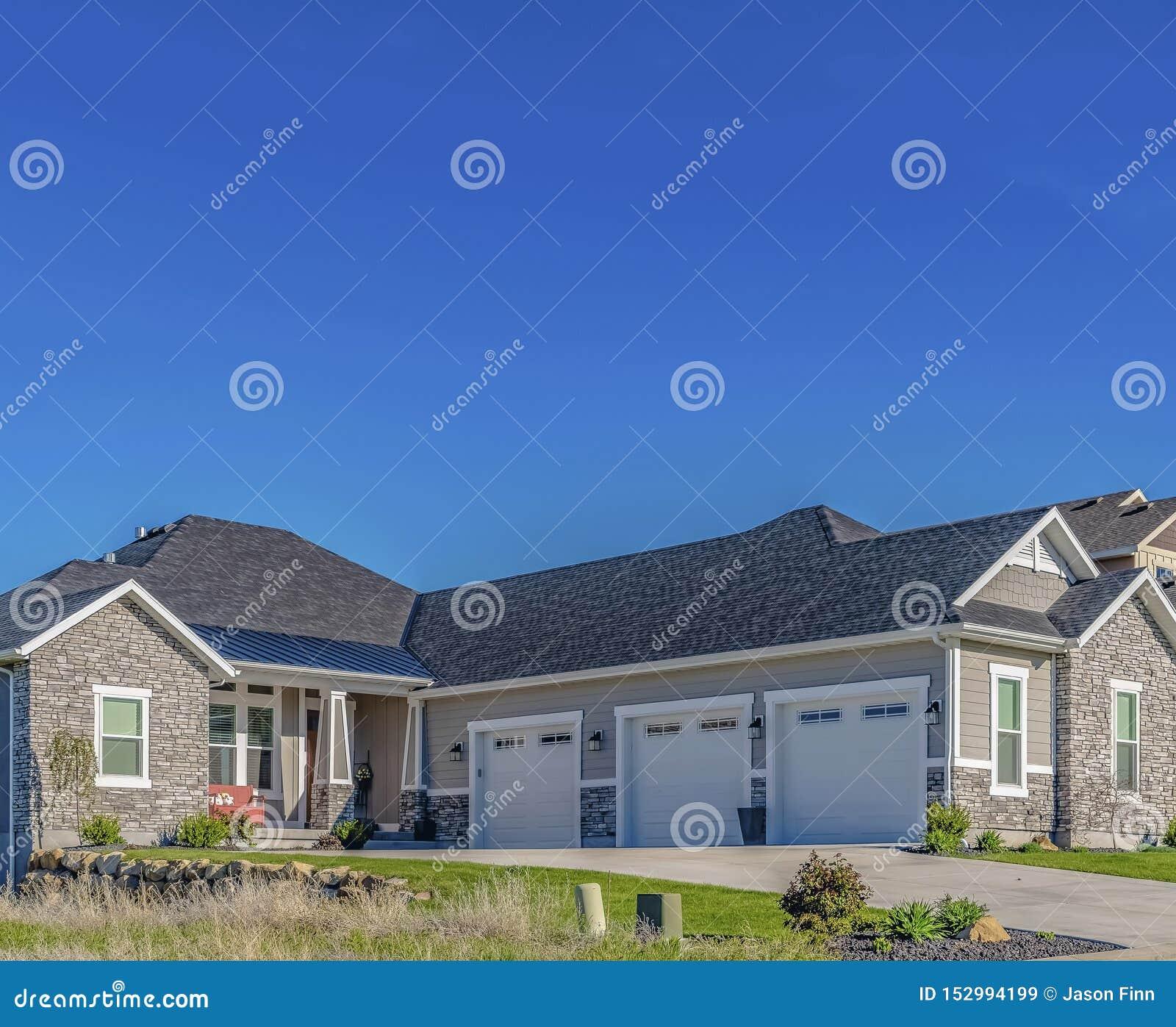 Voorgevel van huis met concrete oprijlaan voor drie garagedeuren en portiek