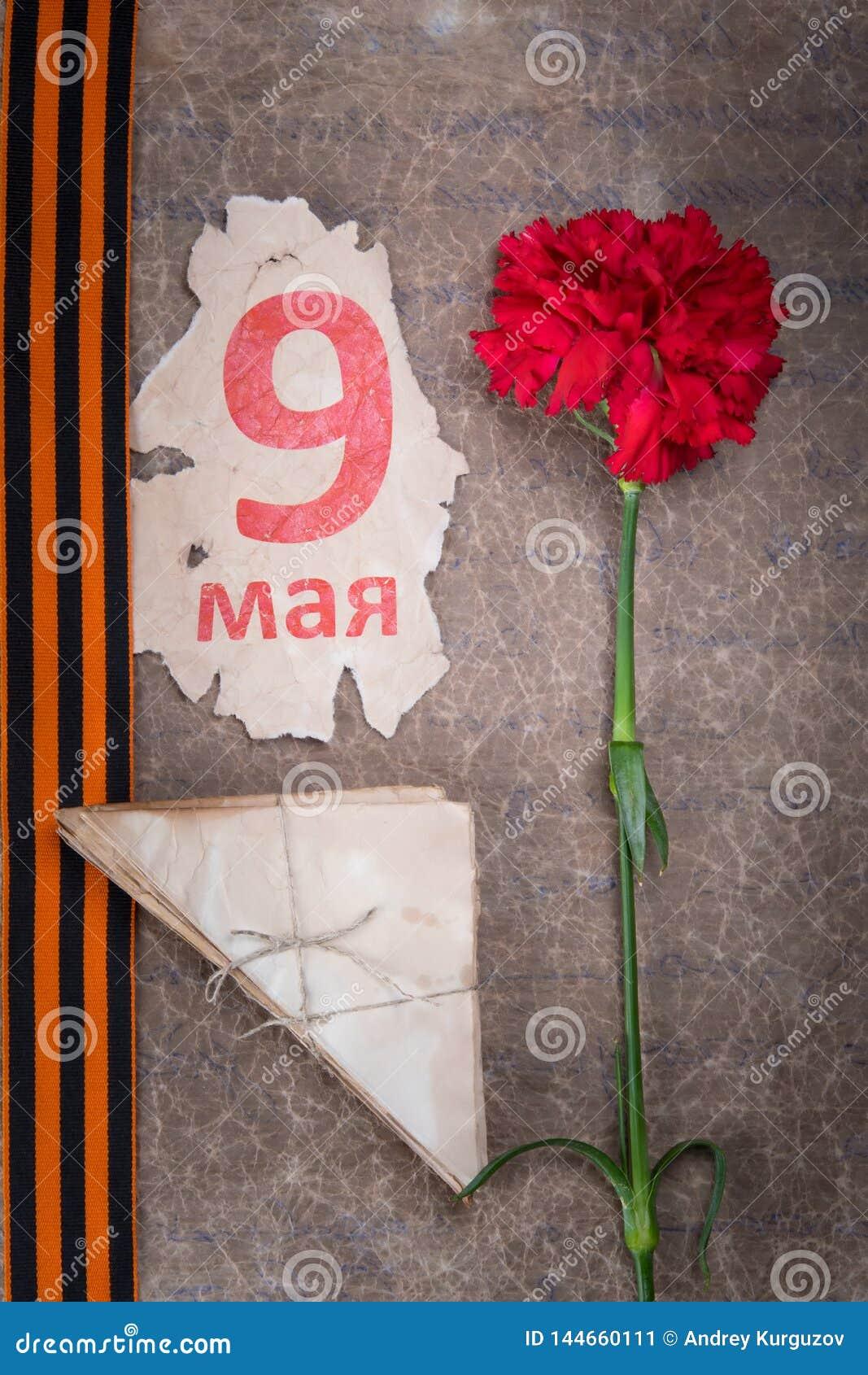 Vor dem hintergrund des alten Papiers, der roten Gartennelke, St- Georgebandes, der Umschläge und eines Kalenderblattes mit der