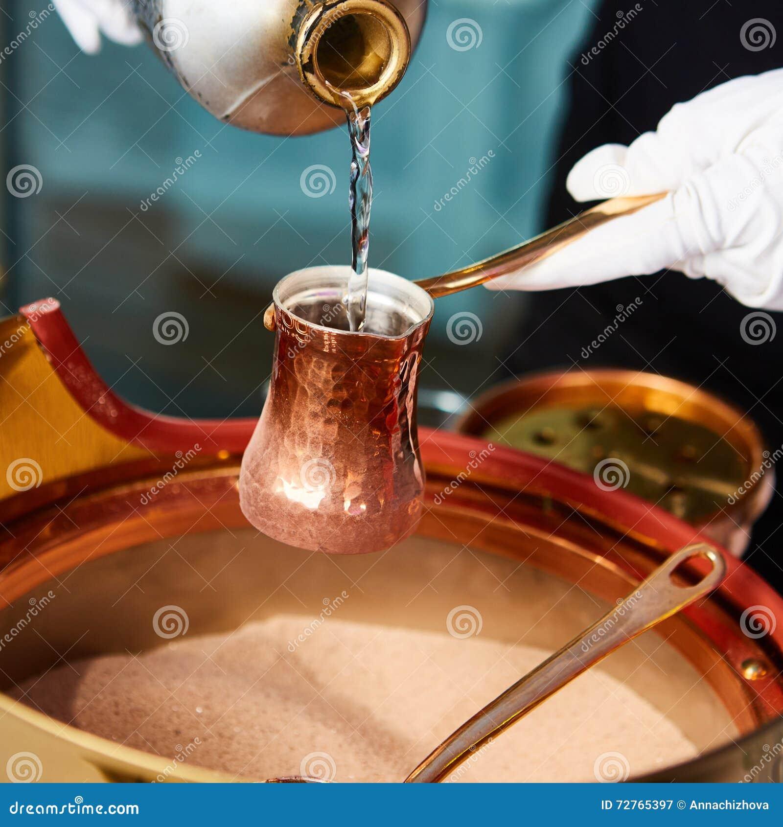Vorbereitung des türkischen Kaffees im cezve im Sand an der Cafébar