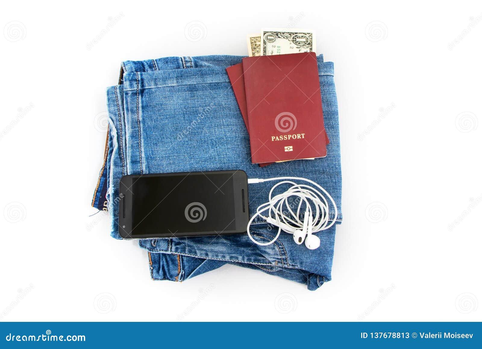Vorbereitung für Reise, Pass, Geld, Telefon mit Kopfhörern auf Jeans lokalisierte weißen Hintergrund
