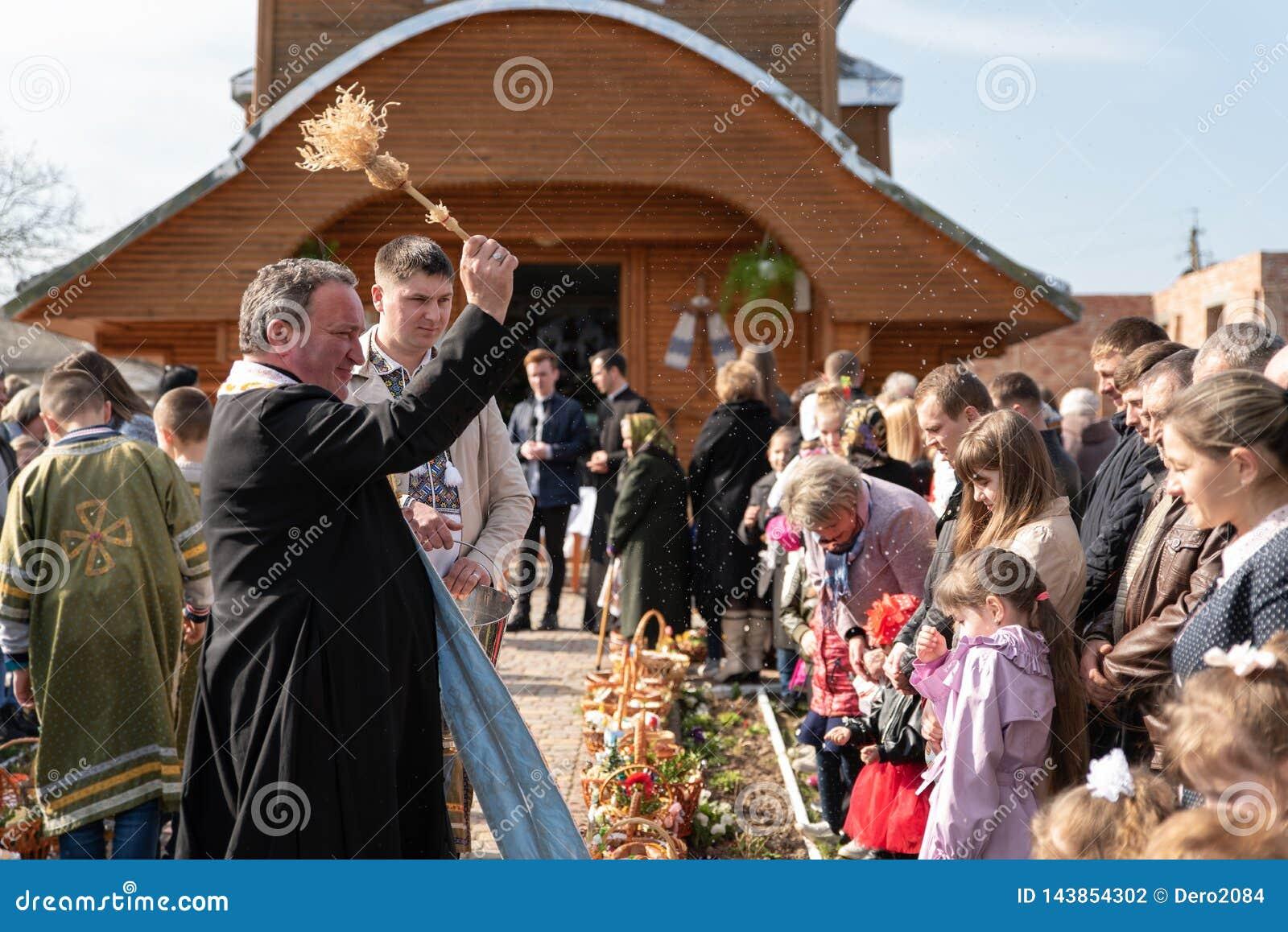 Voroblevychi village, Drohobych district, Ukraine - April 07, 2018: Priest consecrates Easter baskets with food