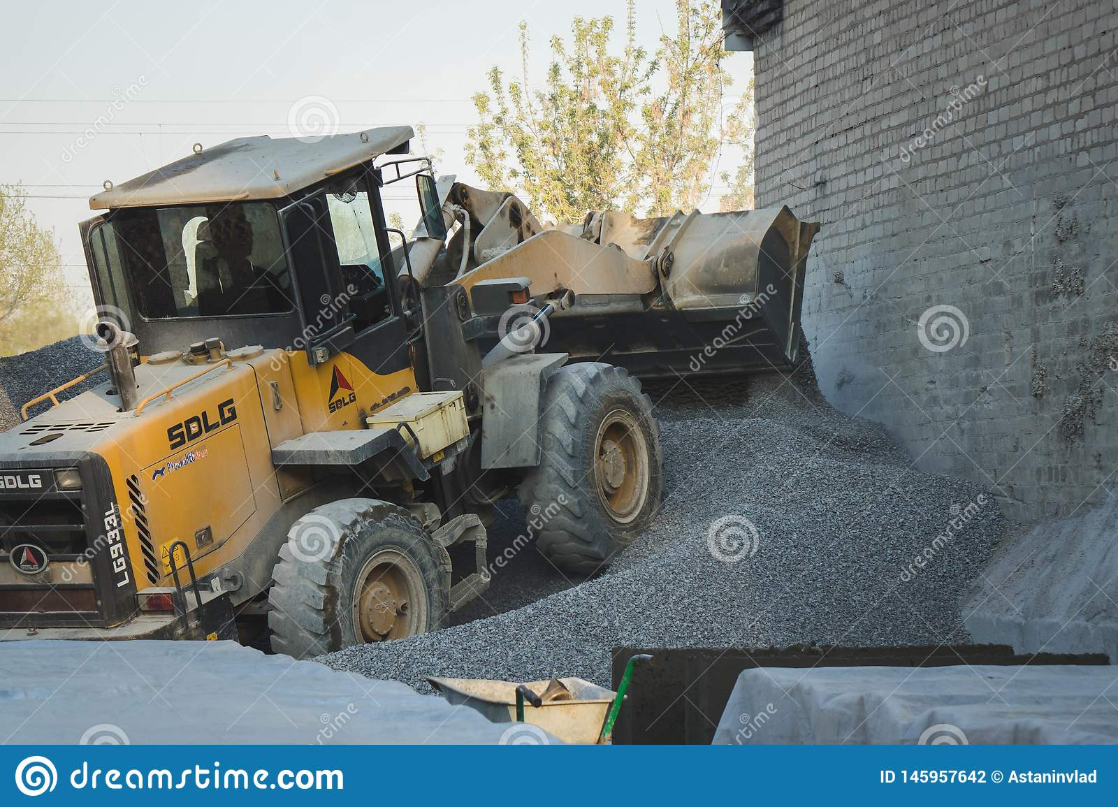 Voronezh region, Russia, april, 25 2019. Tractor loads crushed stone in the production of concrete. Yellow tractor loader running