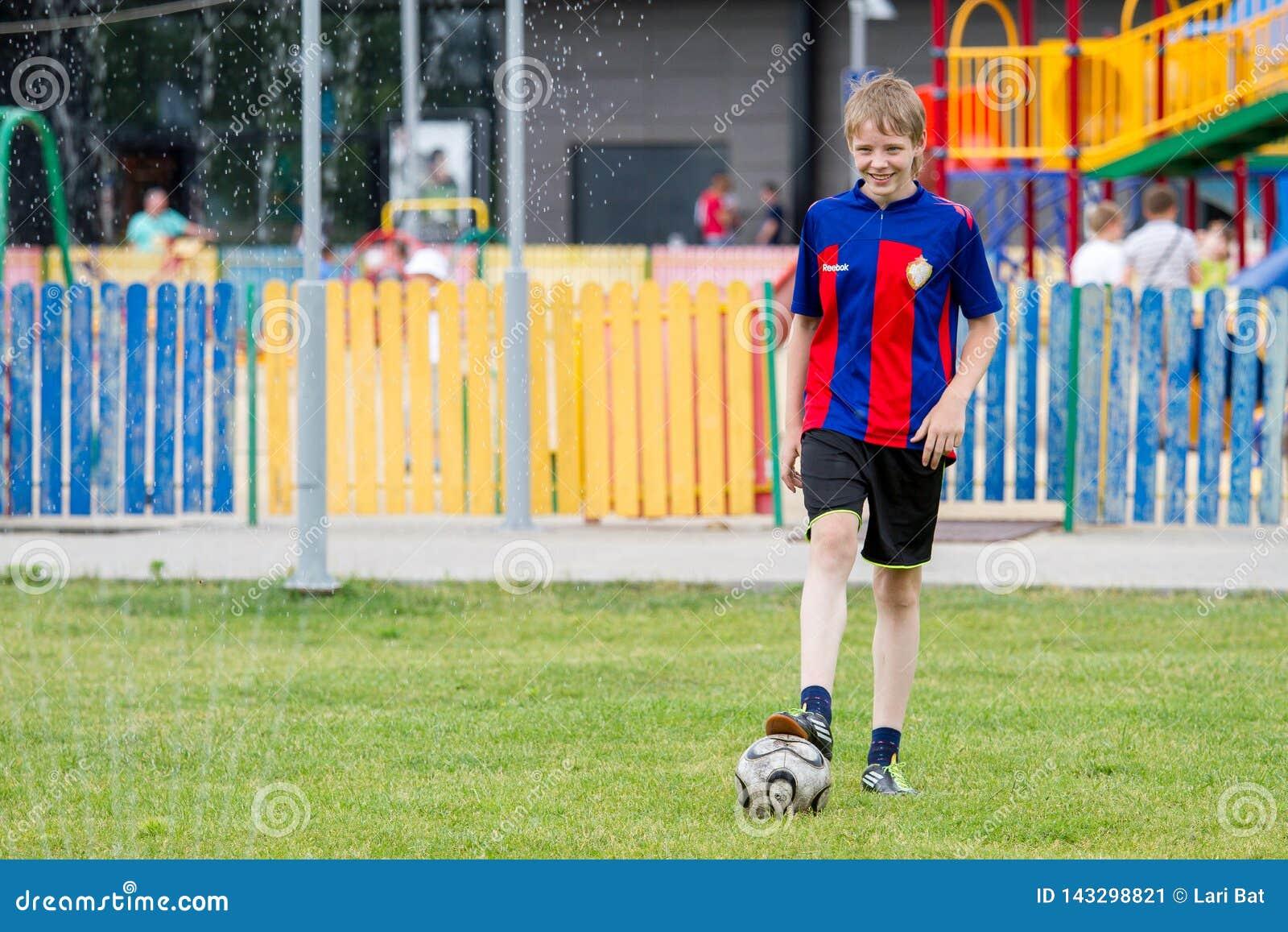 Voronezh, Rosja: Czerwiec 17, 2013 Chłopiec bawić się futbol na gorącym słonecznym dniu
