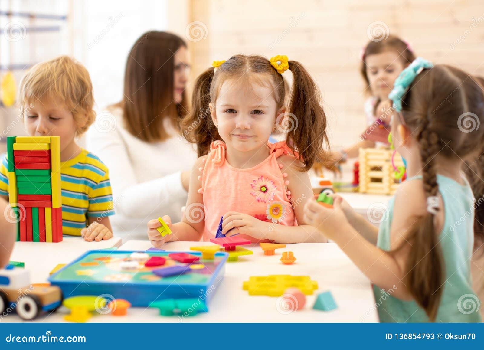 Vorschulkinderspiel mit bunten didaktischen Spielwaren am Kindergarten