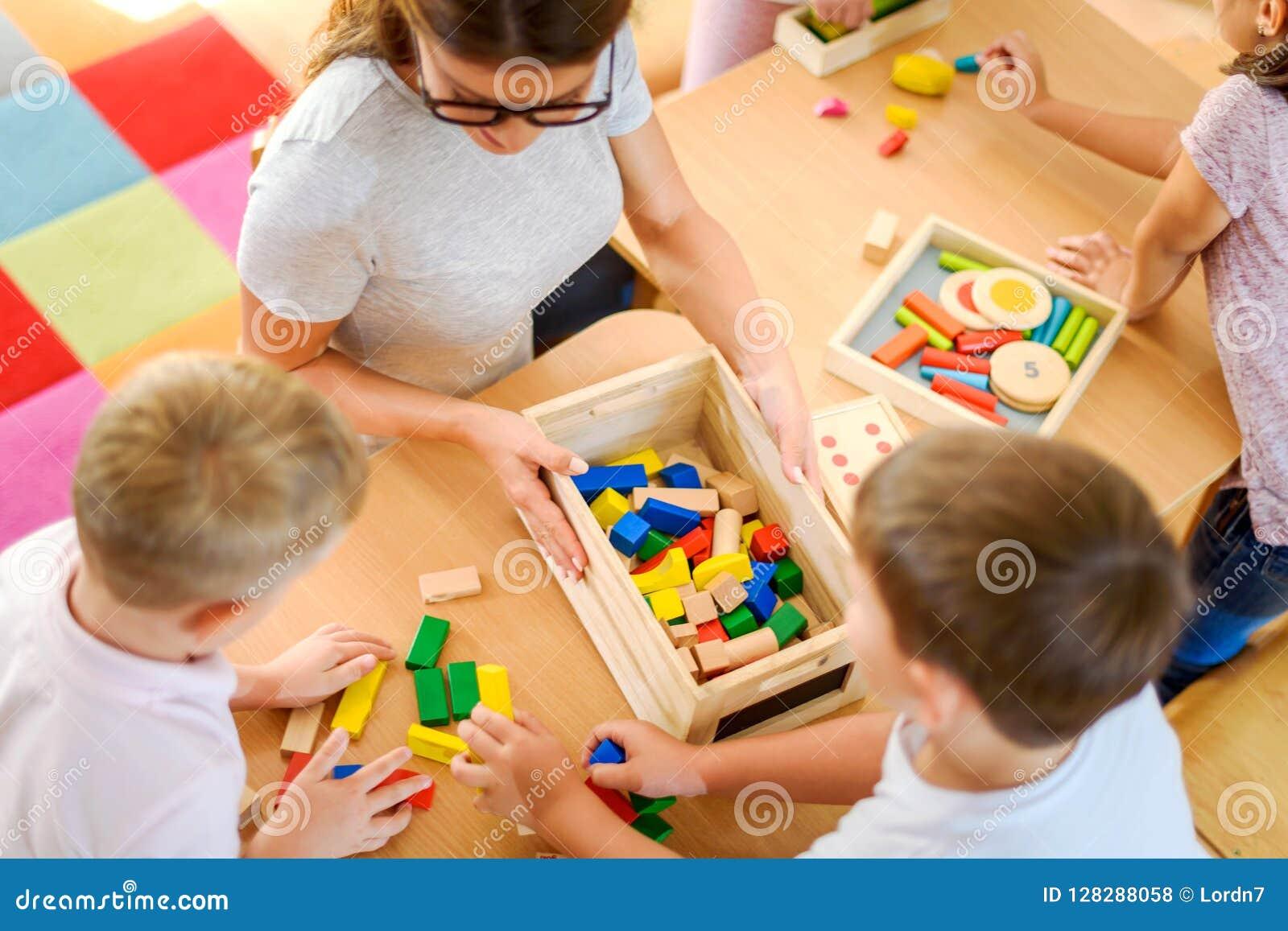 Vorschullehrer mit den Kindern, die mit bunten didaktischen Spielwaren am Kindergarten spielen