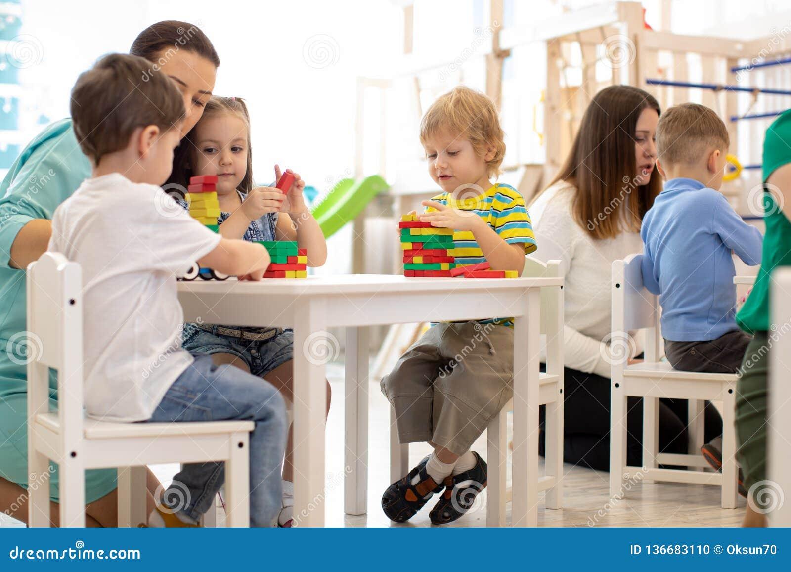 Vorschullehrer mit den Kindern, die mit bunten hölzernen pädagogischen Spielwaren am Kindergarten spielen