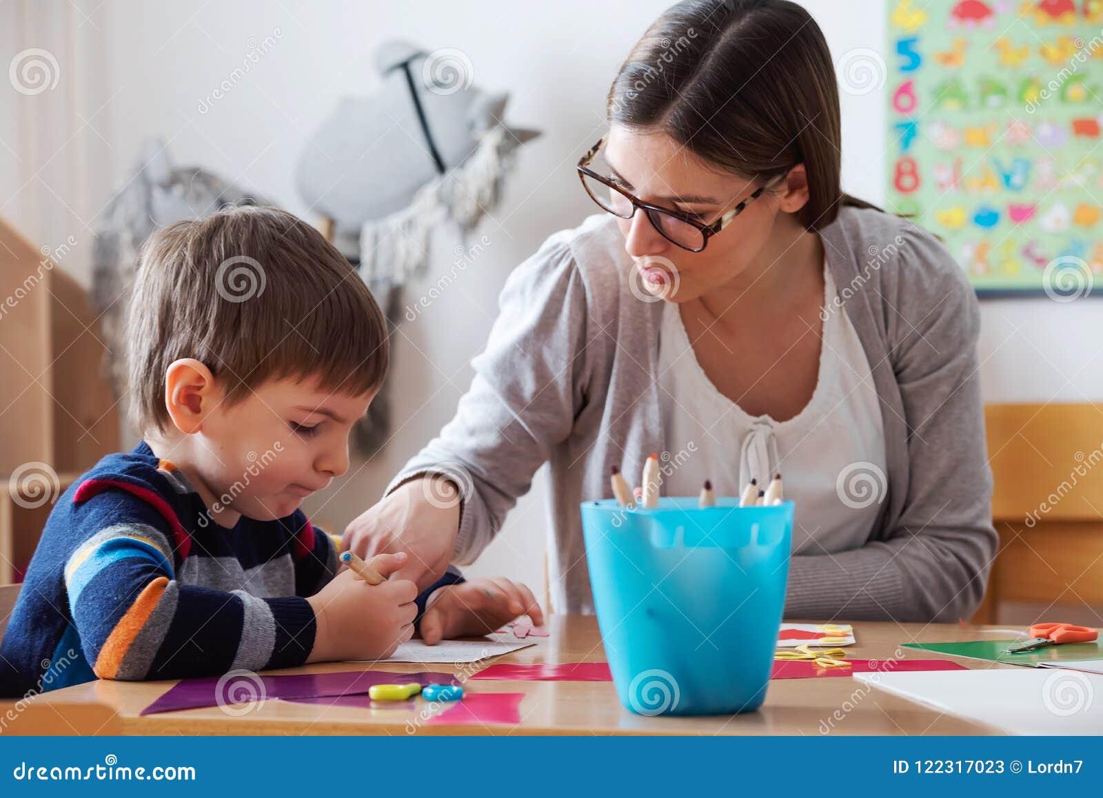 Vorschullehrer mit Kind am Kindergarten - kreativer Art Class