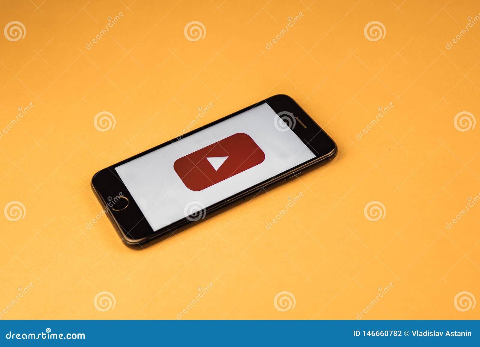 Votary Rosja - mog? 03, 2019: Brandnew Jab?czany iPhone 7 z logo YouTube na pomara?czowym tle, YouTube jest popularny