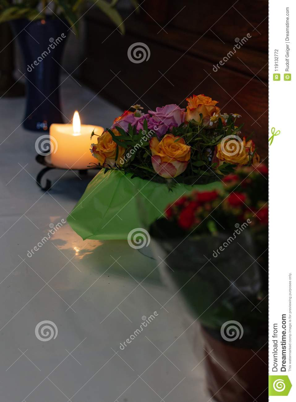 votive altar in church with green and pink flowers