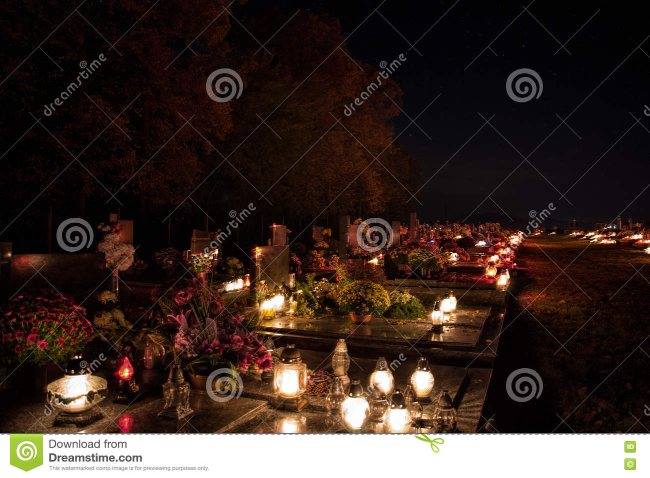 Votive candles lantern burning on the graves in Slovak cemetery at night time. All Saints  Day. Solemnity of All Saints
