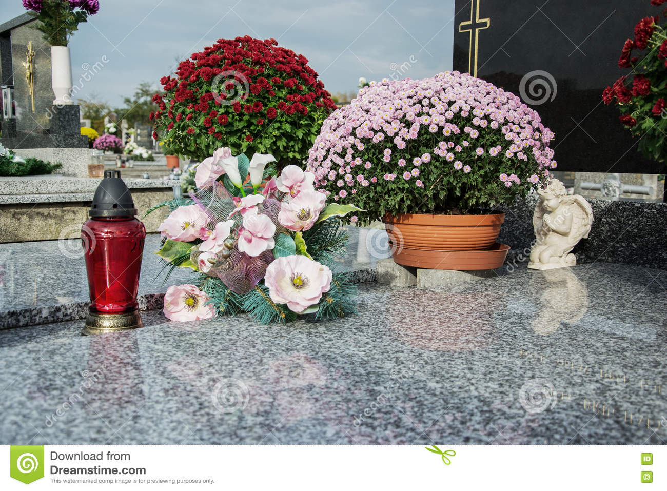 Votive candles lantern and chrysanthemum flowers on tomb stones in graveyard. Graves, tombstones on traditional cemetery