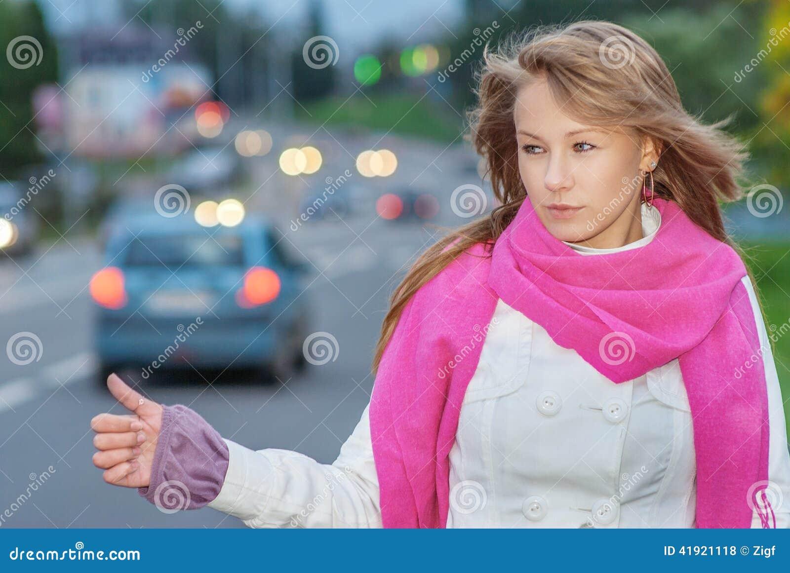 Voto hermoso de la mujer joven en el camino de ciudad