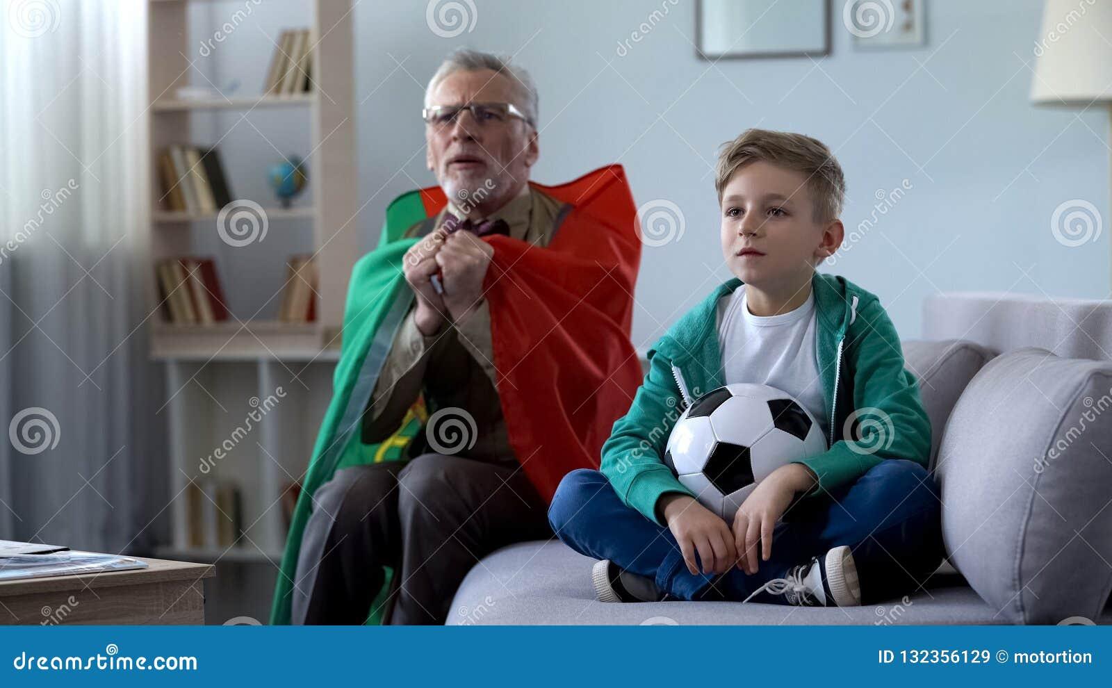 Vovô envolvido no futebol de observação da bandeira portuguesa com o menino, preocupando-se sobre o jogo
