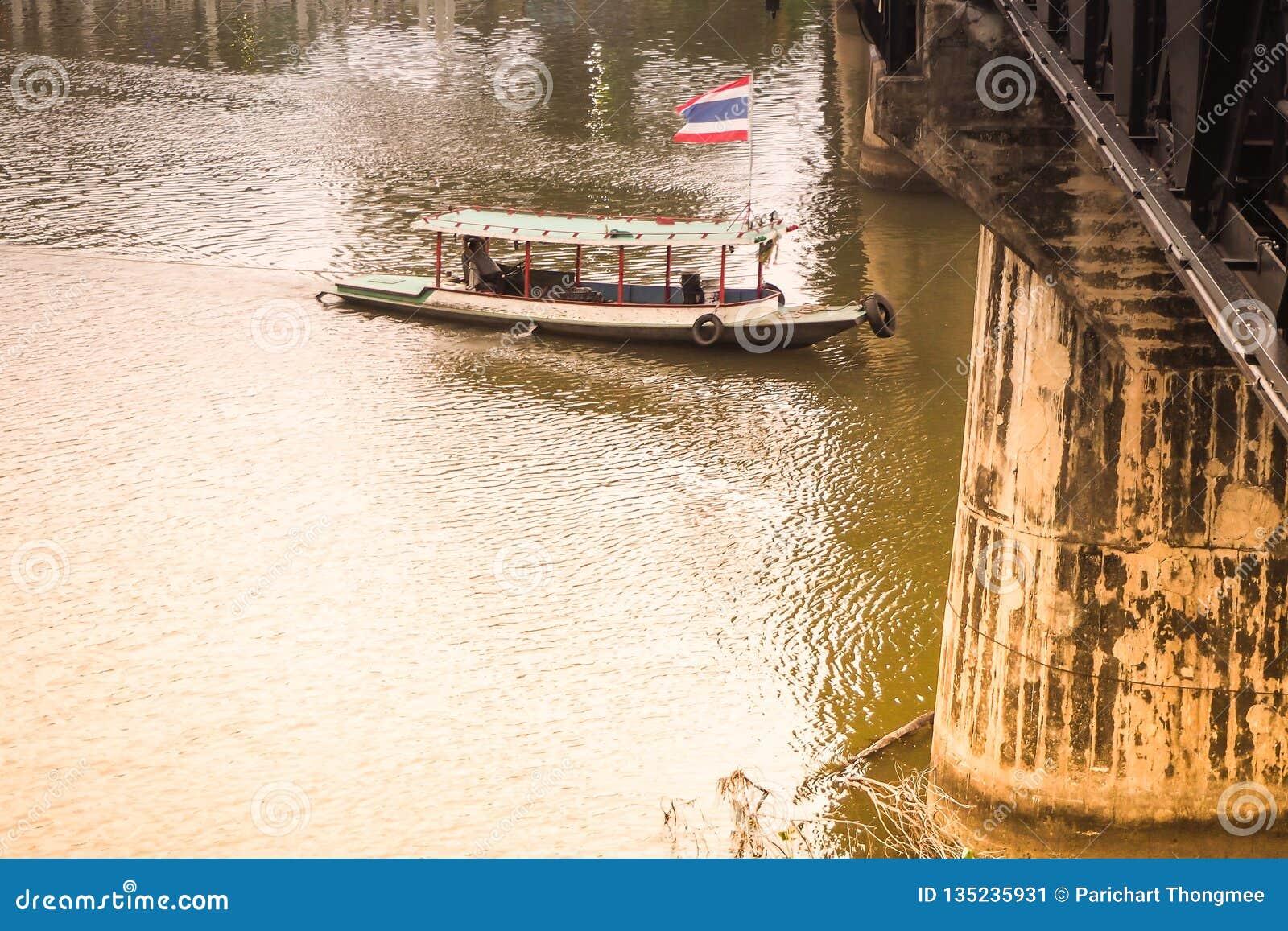 Voyage de touristes en conduisant le bateau et le pont au-dessus du point de repère historique principal de Kwai de rivière de Ka