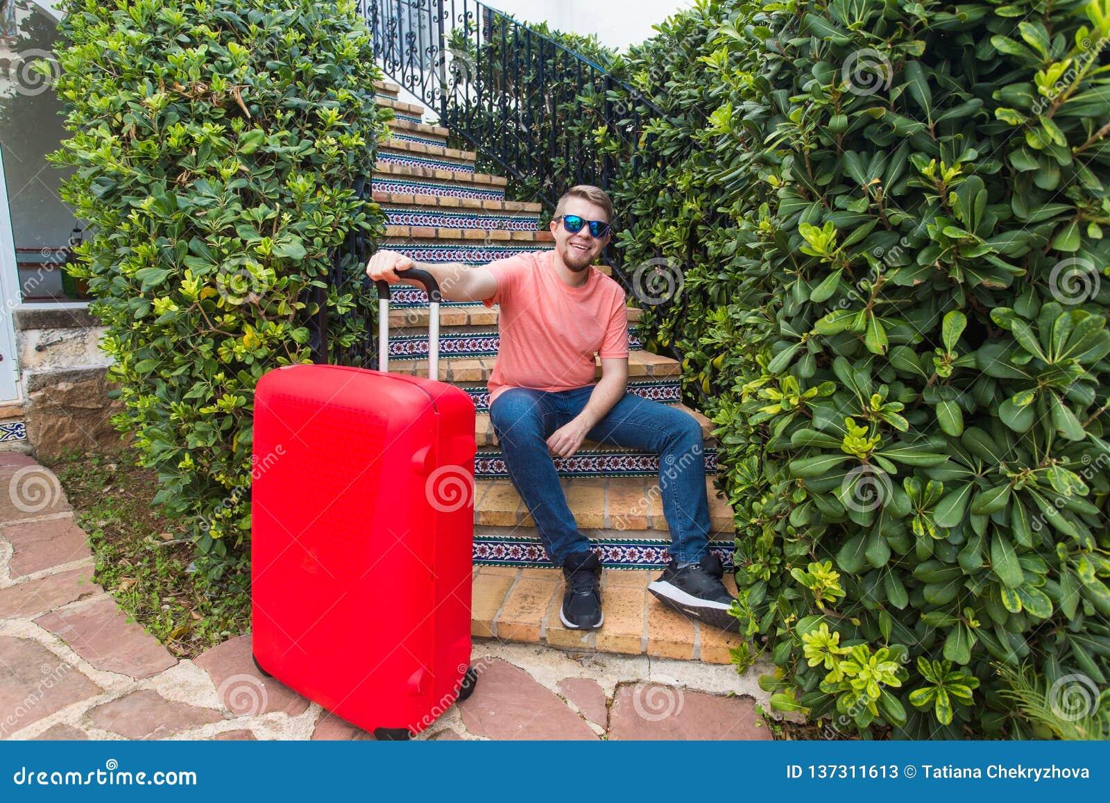 Voyage, vacances et concept de personnes - touriste beau heureux d homme s asseyant sur des escaliers avec la valise et le sourir
