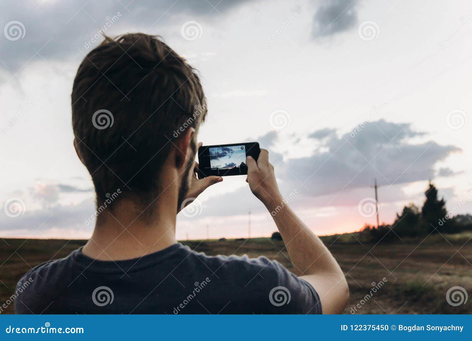 Voyageur élégant de hippie tenant le téléphone intelligent prenant la photo du bea