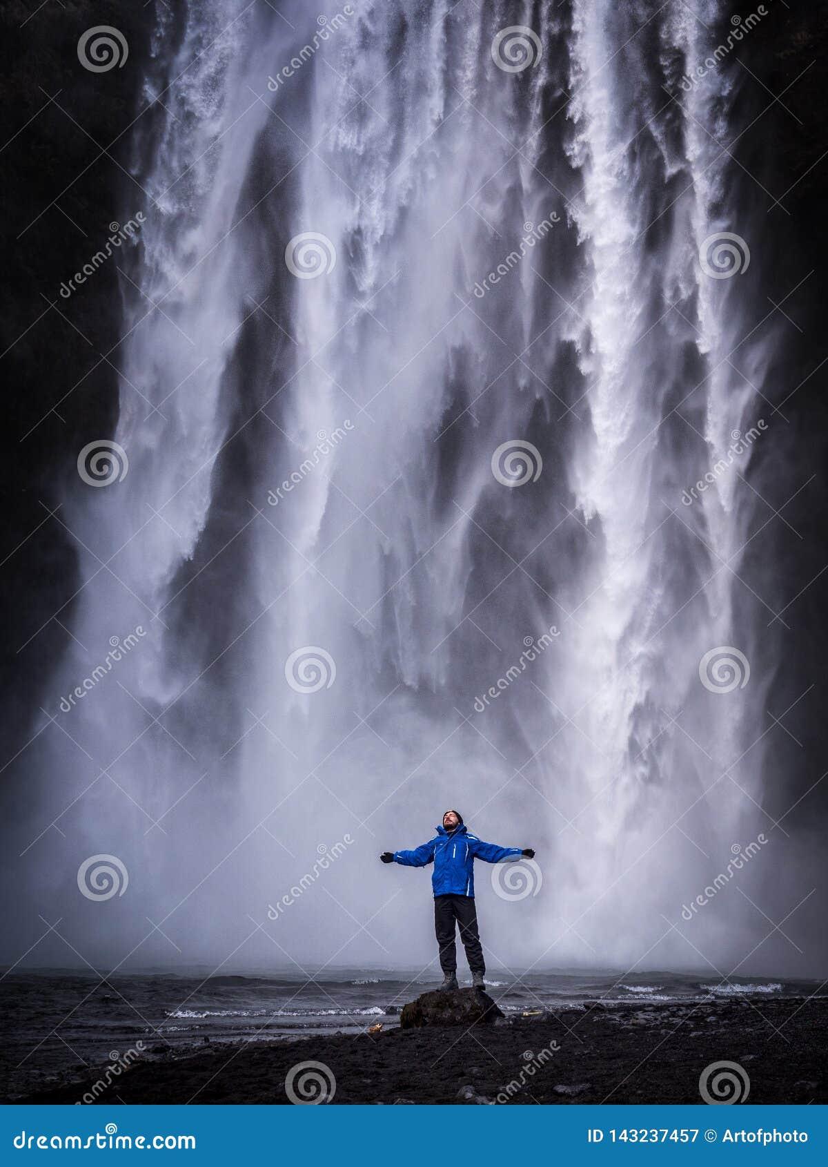 Voyageur avec les bras tendus près de la cascade en Islande