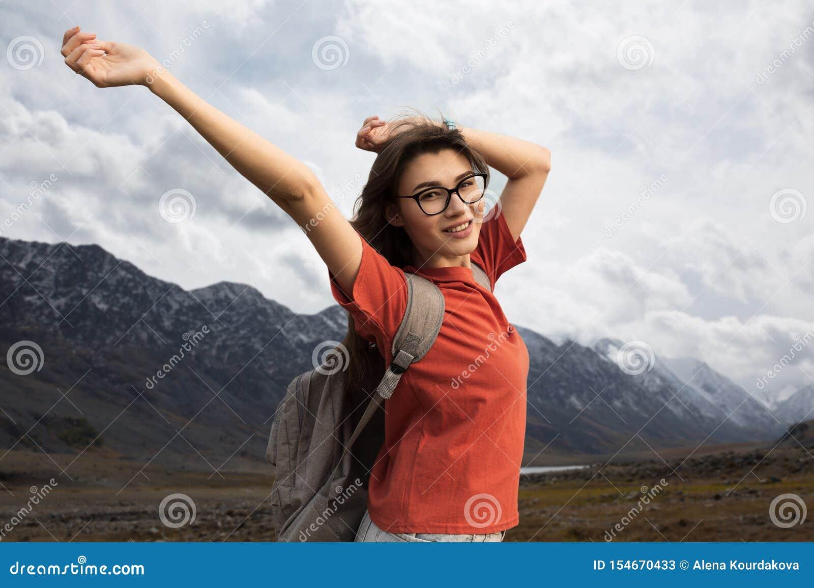 Voyageur de femme avec le sac à dos souriant supportant ses bras La beauté de la nature, montagnes neigeuses