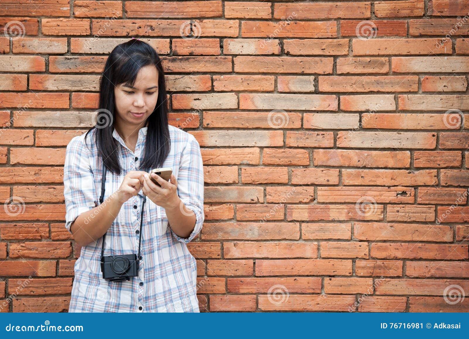 Voyageur féminin à l aide du smartphone avec le fond de mur de briques