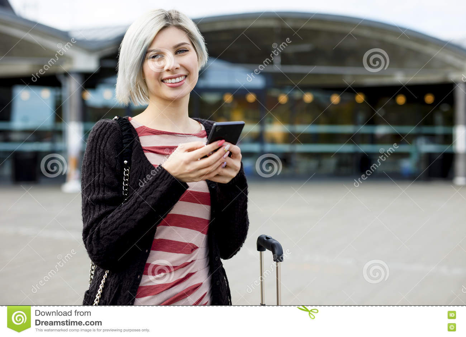 Voyageur féminin de sourire à l aide du téléphone intelligent en dehors de la station de train