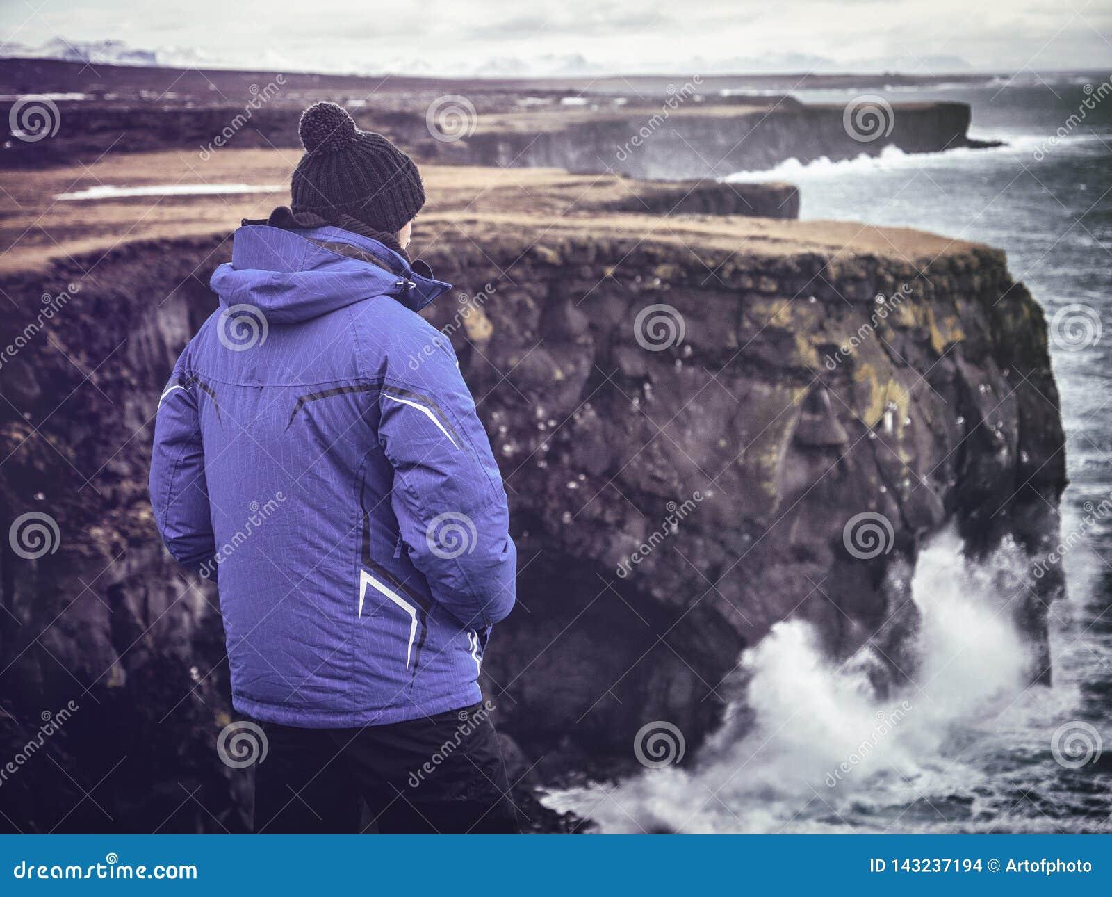Voyageur masculin regardant la mer orageuse de la falaise