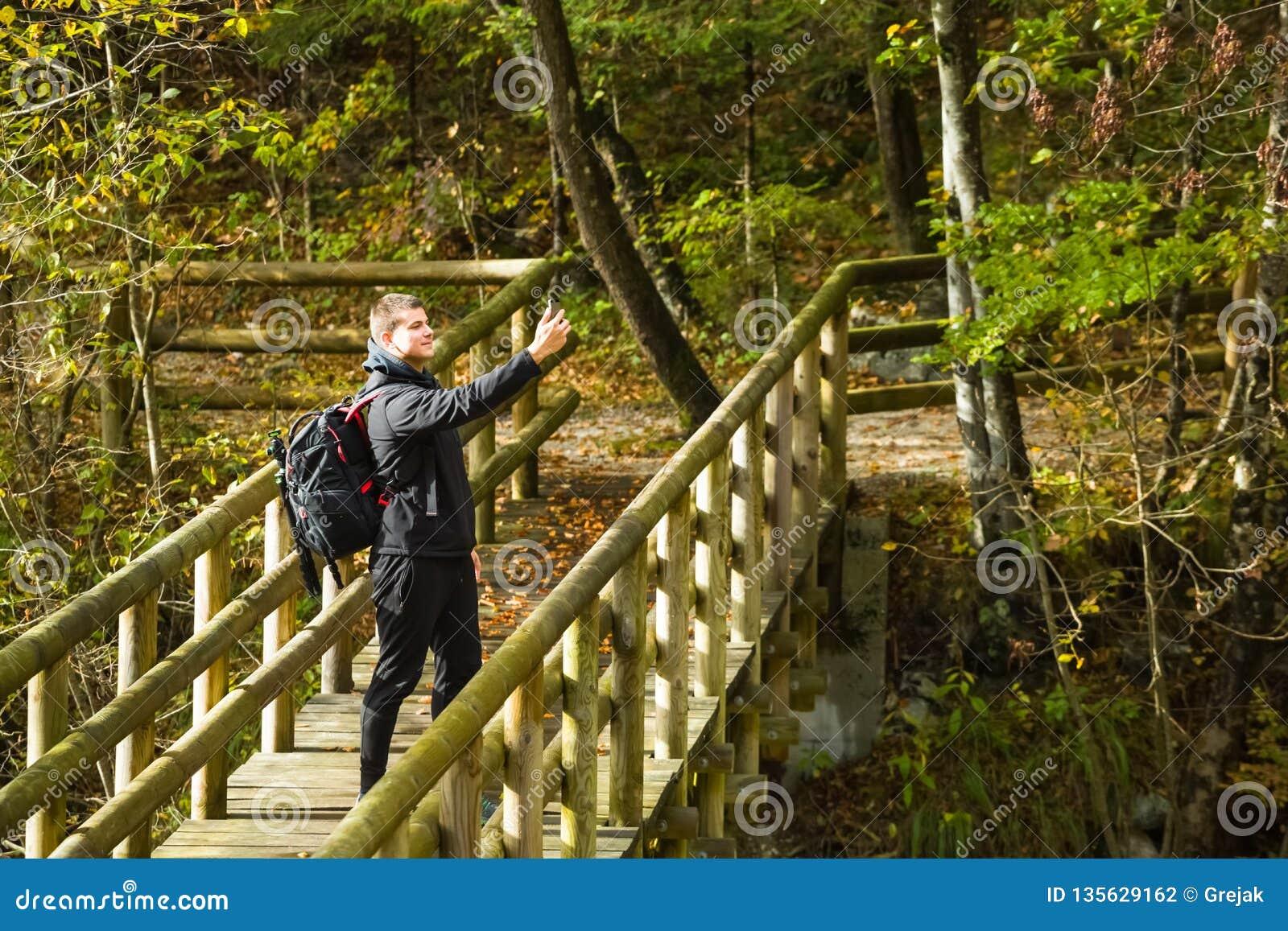 Voyageur prenant le selfie avec le smartphone sur le pont en bois dans la forêt