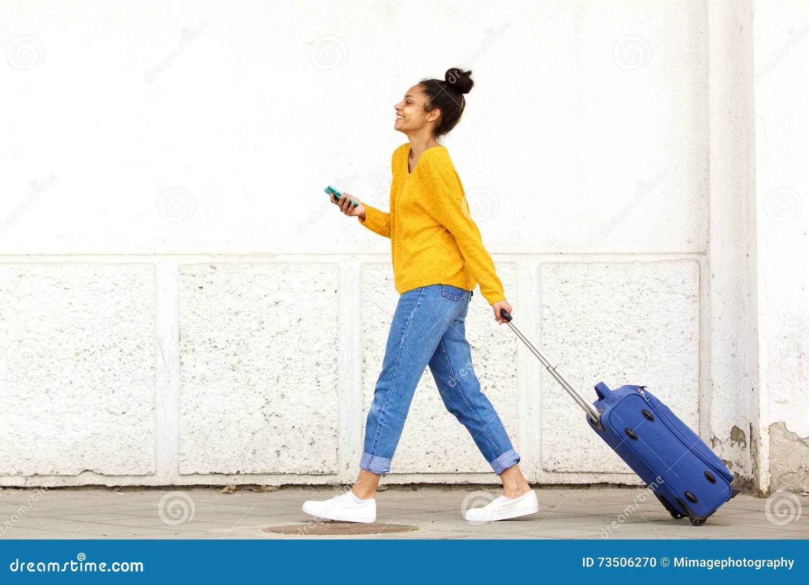 Voyageuse de femme avec le bagage et le téléphone portable