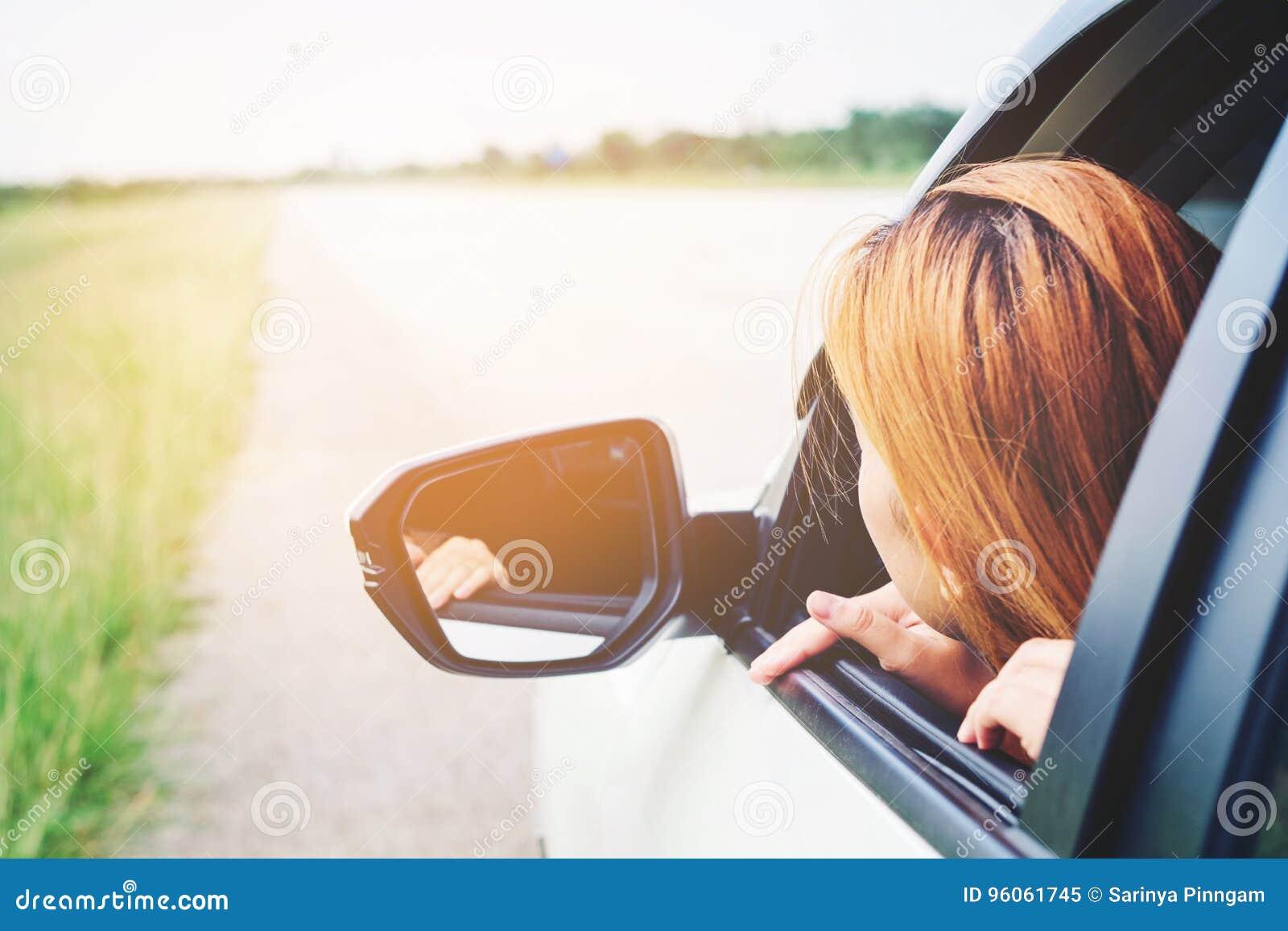 Voyageuse de femme d Asain avec la voiture sur la belle route