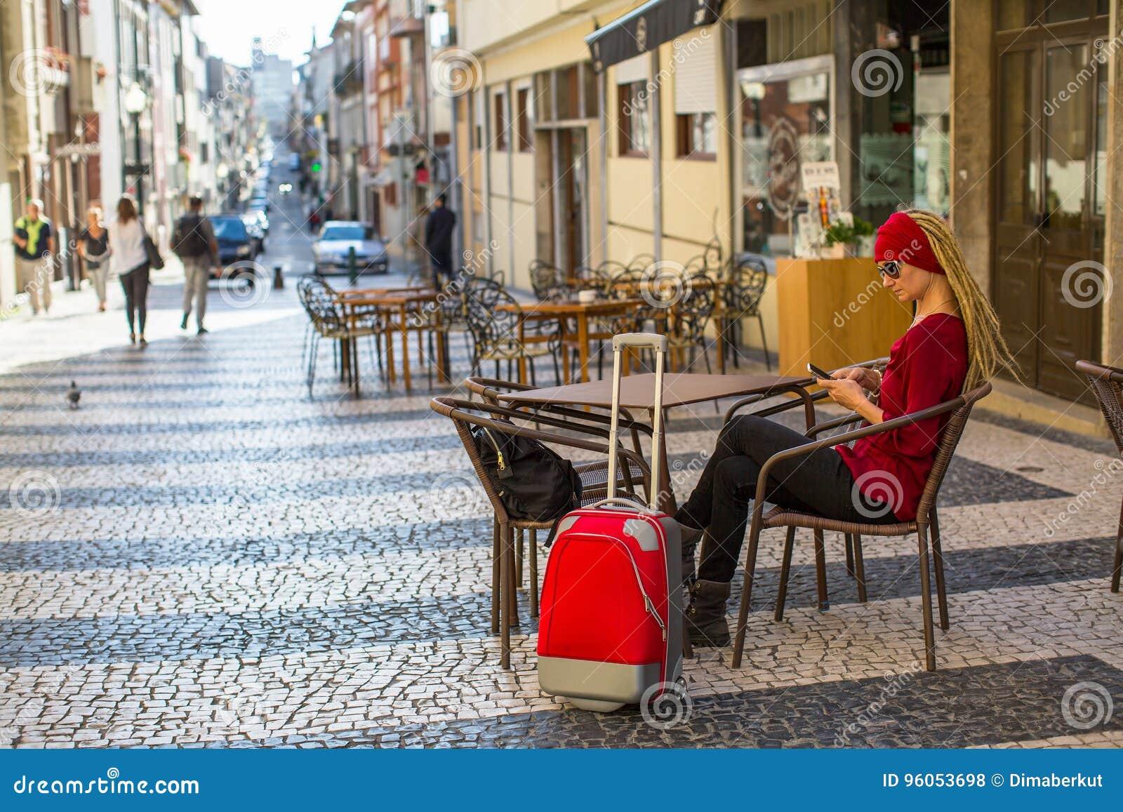 Voyageuse de jeune femme avec une valise se reposant dans un café de rue avec un smartphone