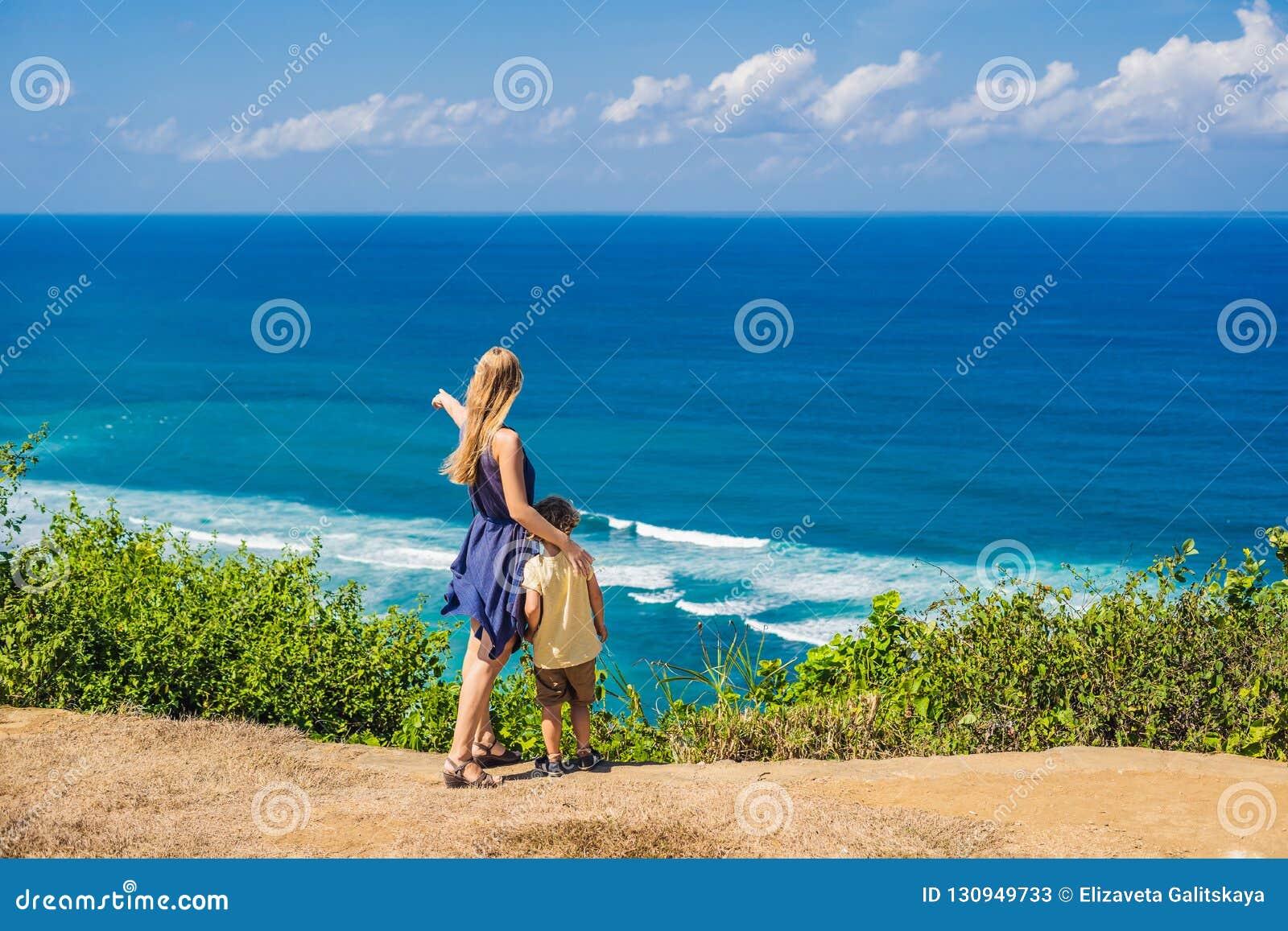 Voyageuses de maman et de fils sur une falaise au-dessus de la plage Paradis vide