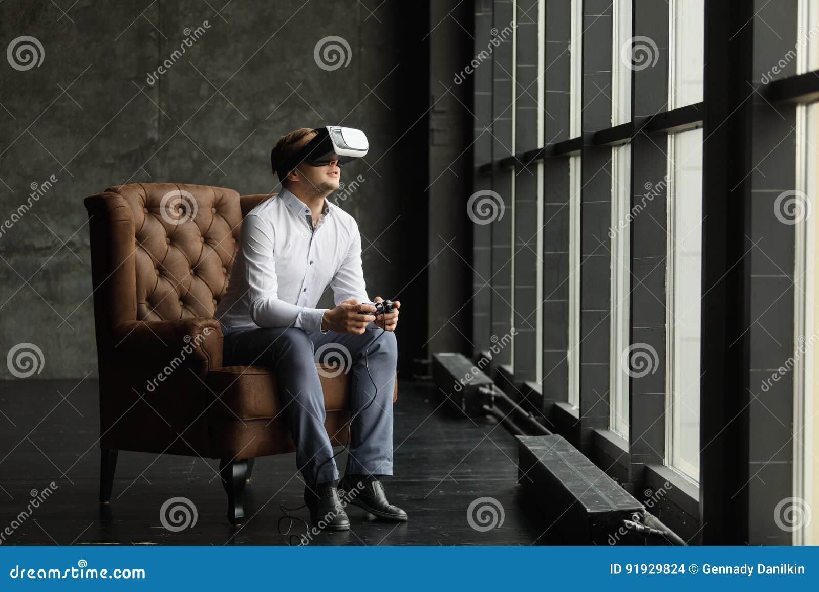 d15d06f70219 Man wearing virtual reality goggles. Interior shot