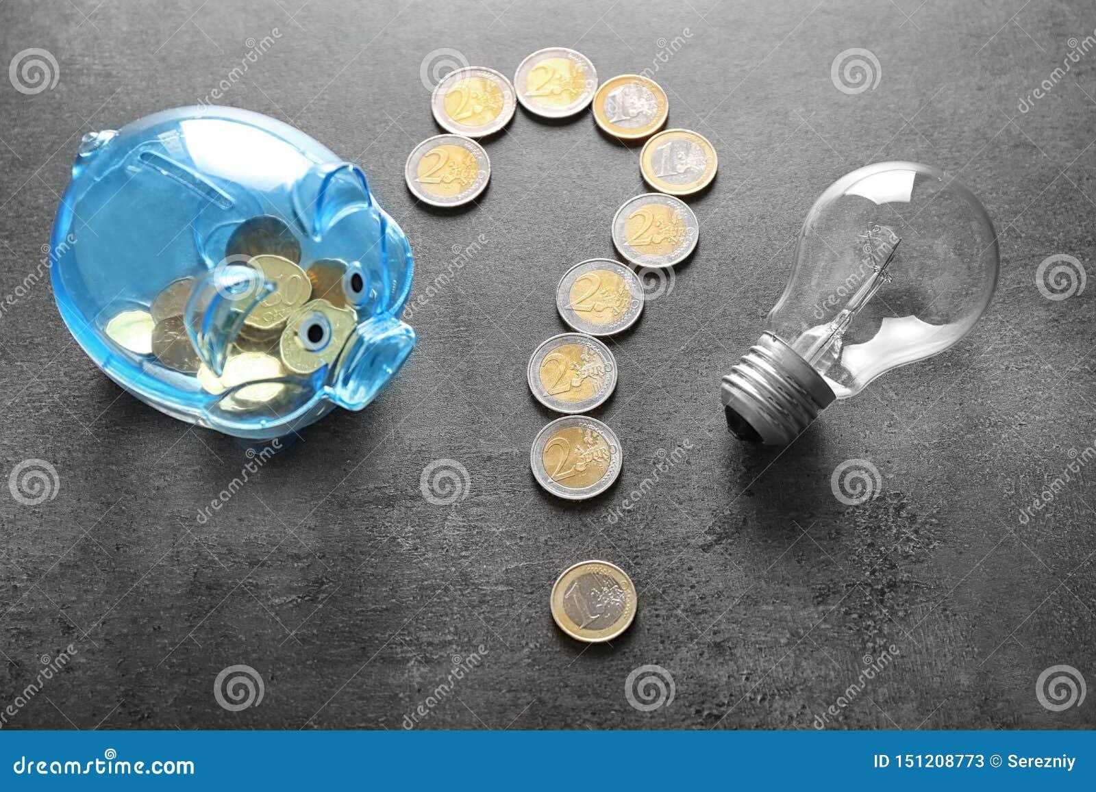 Vraagteken van muntstukken, spaarvarken en gloeilamp op grijze achtergrond wordt gemaakt die Het concept van de elektriciteitsbes