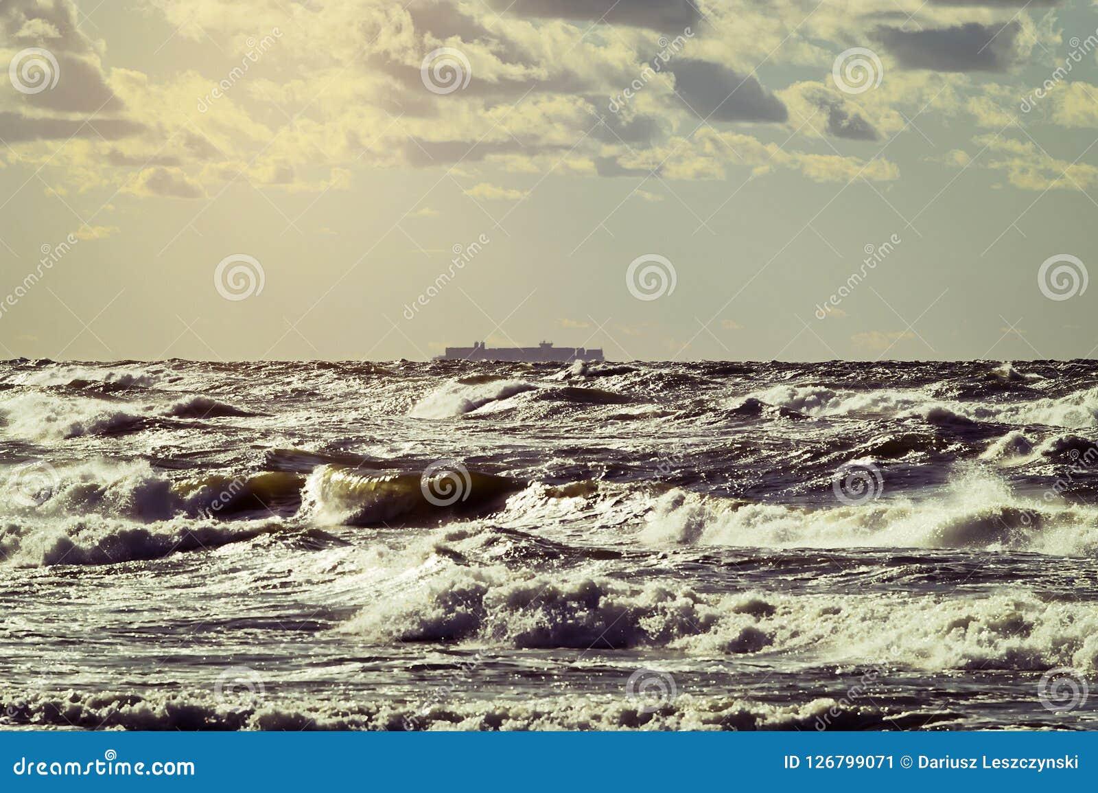 Vrachtschipsilhouet op de horizon Groot containerschip die door stormachtige golven van de Oostzee varen