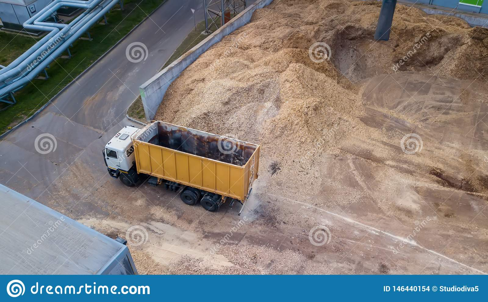 Vrachtwagen dichtbij een stapel van zaagsel, de mening van de hommel