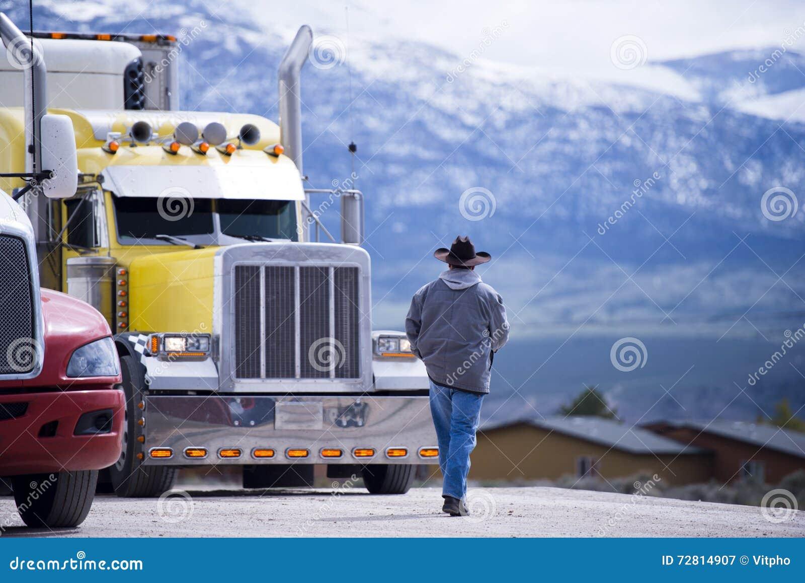 Vrachtwagenchauffeur die naar aangepaste indrukwekkende gele semi vrachtwagen gaan