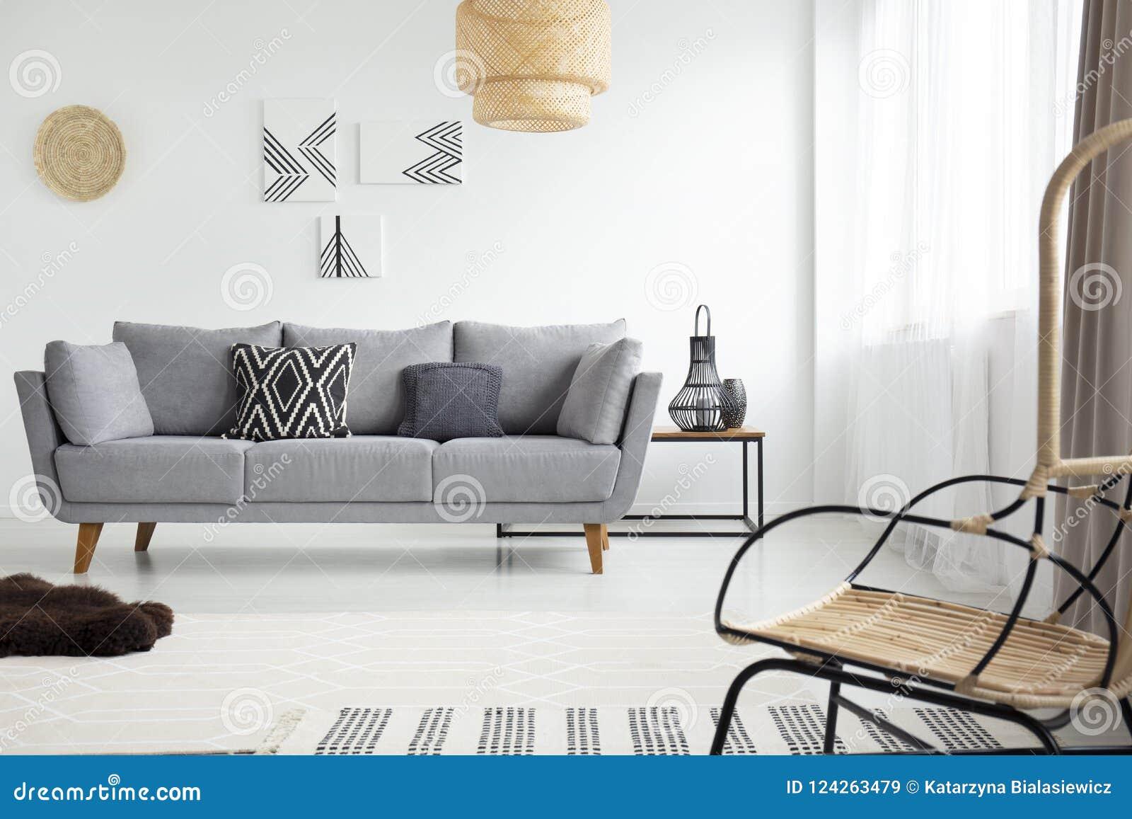 Vraie photo d un fauteuil de rotin vis-à-vis d un canapé gris dans le scandi