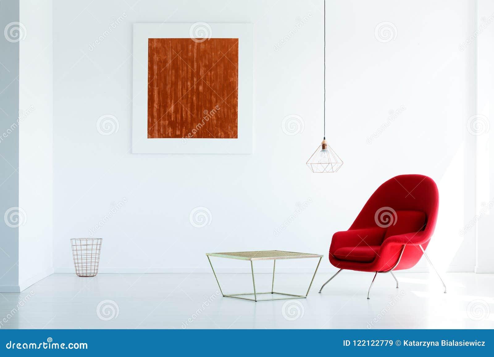 Vraie photo d un fauteuil rouge se tenant à côté d une table en métal dans W