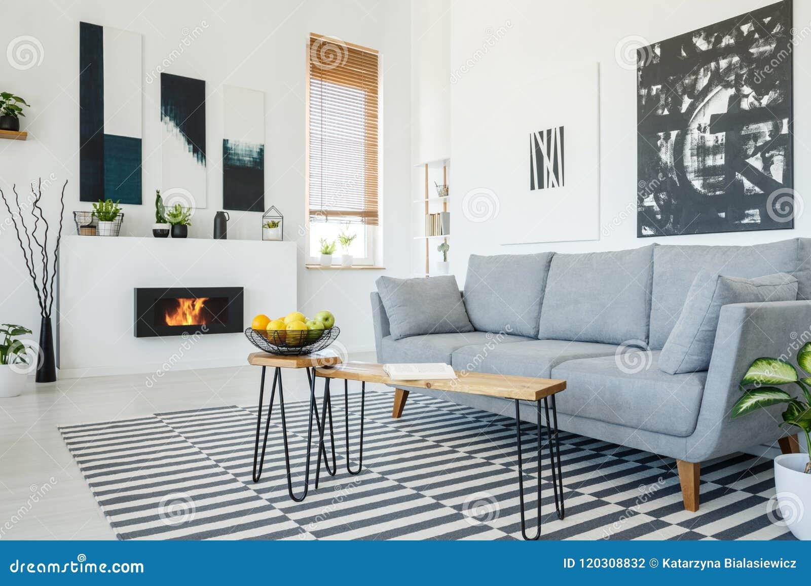 Vraie photo d un sofa gris se tenant devant une table en bois dedans